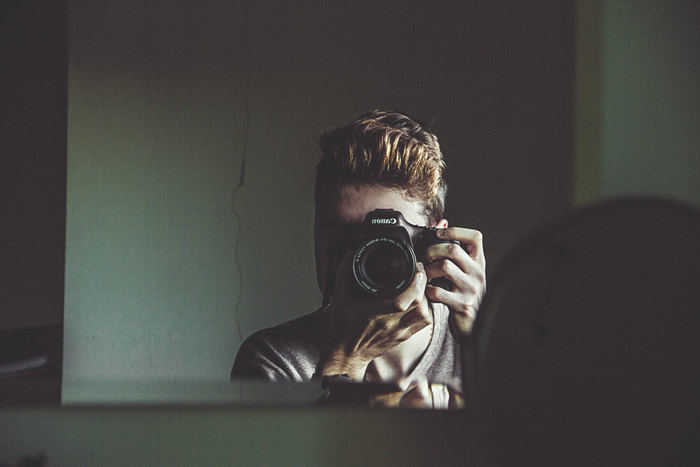 A male photographer talking a self portrait of himself through the mirror - photography themes