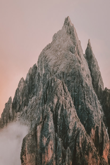 a rocky mountaintop against a soft pink sky - stunning landscape photos