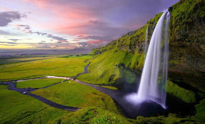 a luscious green mountainous landscape featuring a waterfall at evening - stunning landscape photos
