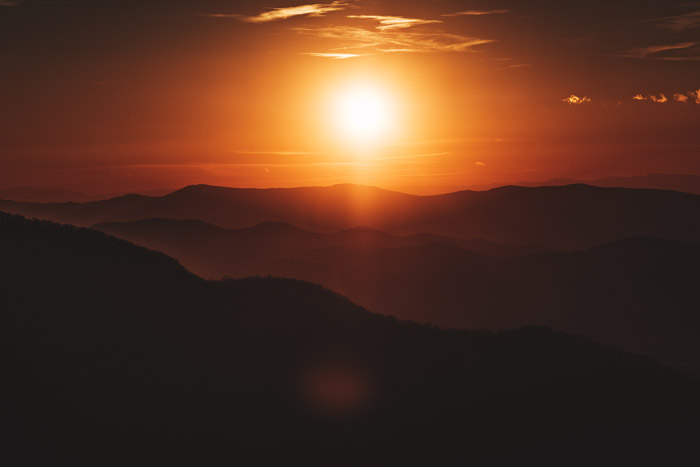 a glorious sunset over a mountainous landscape - stunning landscape photos