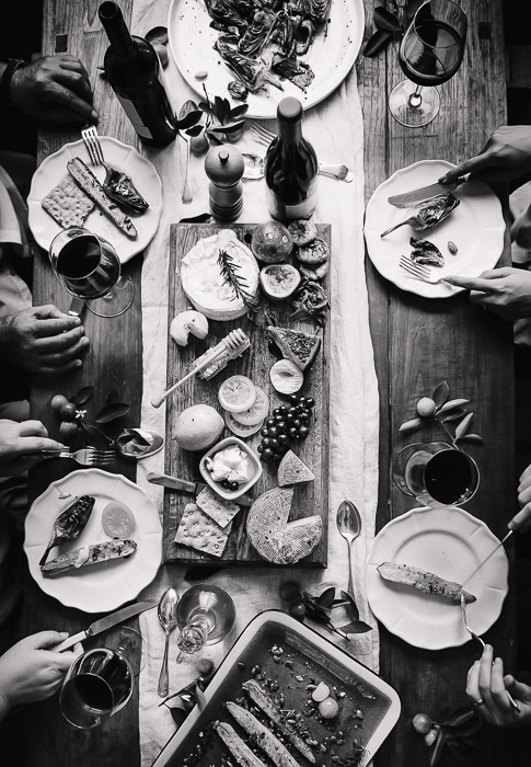 A black and white food photography flatlay of thanksgiving dishes on a wooden table