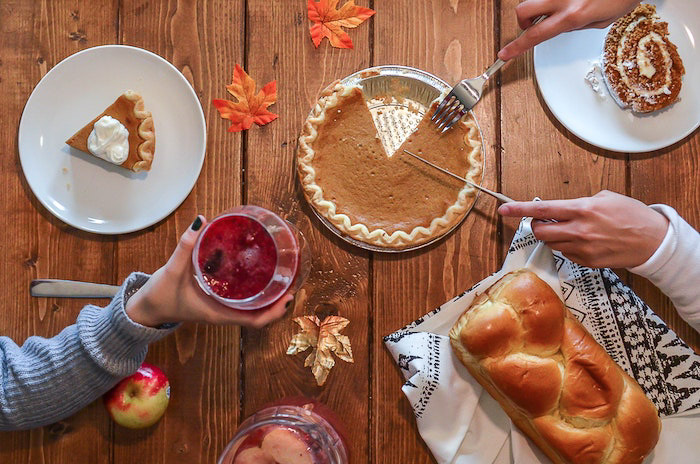 A thanksgiving photography flatlay featuring food and drinks on a wooden table