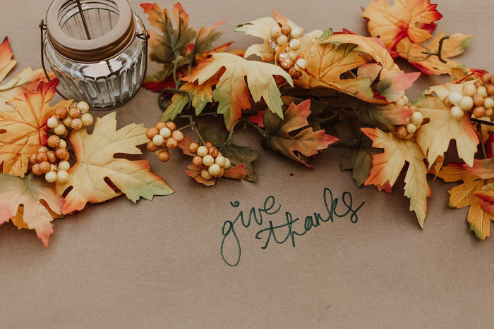 A thanksgiving photography flatlay featuring autumn leaves and a candle