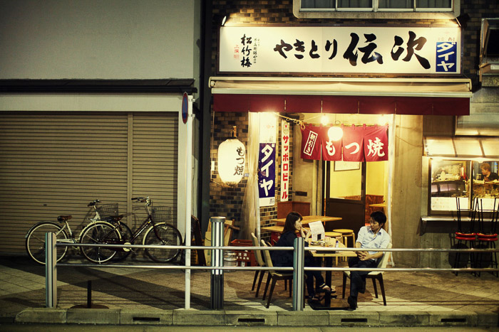 A night street scene of customers outside a cafe