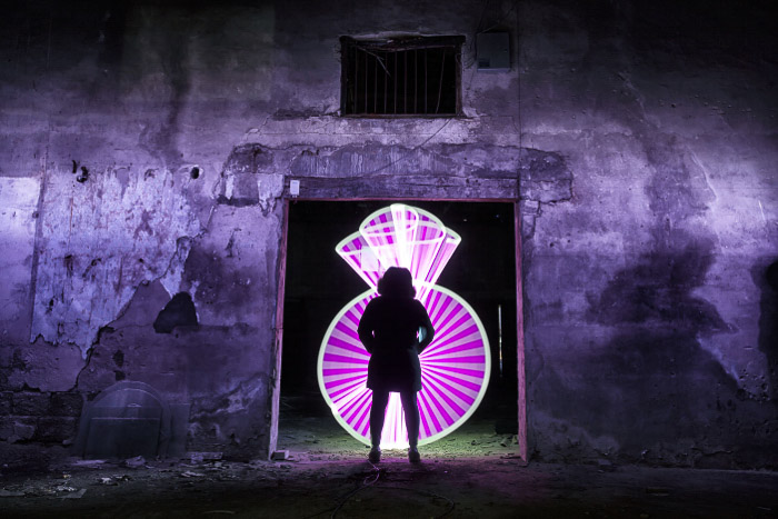 A silhouette of a person standing in front of the doorway of an abandoned building, lit from behind by pink light painting
