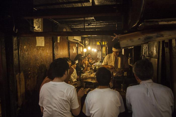 Street shot of vendors at a food stall at night