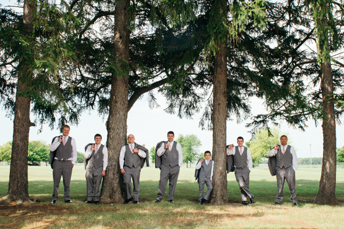 wedding portrait of the groomsmen posing between trees - wedding photography business tips