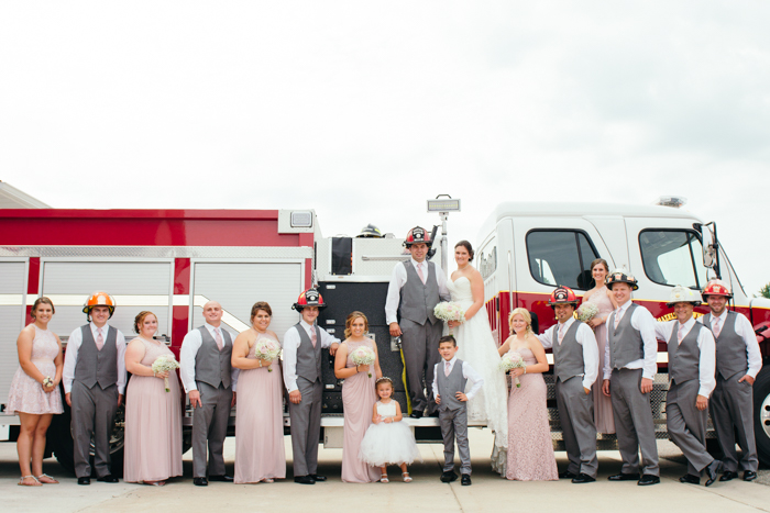 A wedding group photo posed in fireman helmets by a firetruck