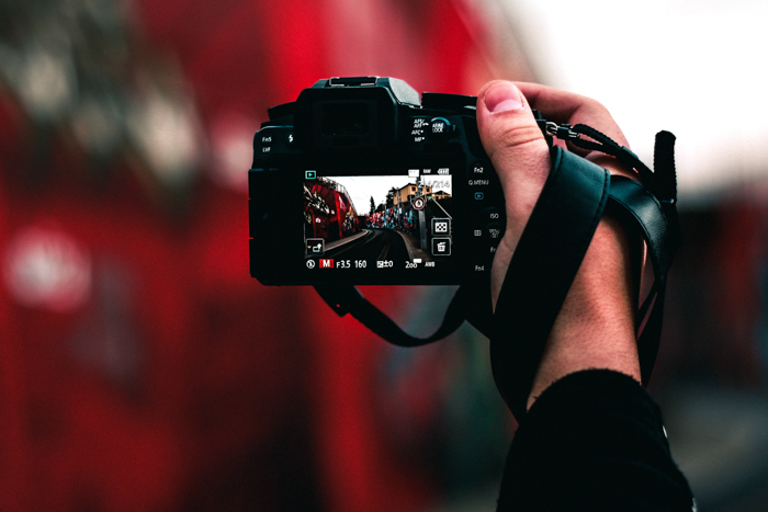 A photographer holding a DSLR camera on a hand strap - B-Grip HS+ Review