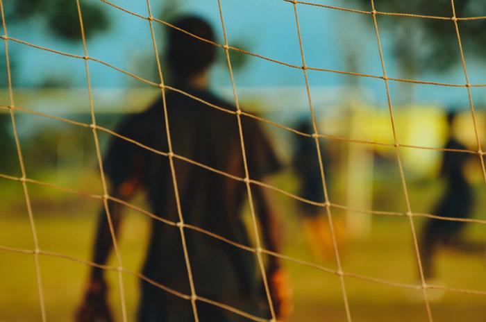 Artistic soccer photography shot of a player shot through the net