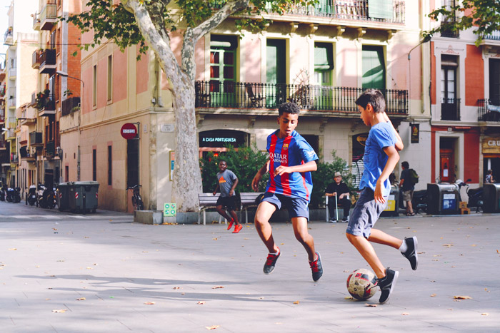 A soccer photo of two boys playing football on the street