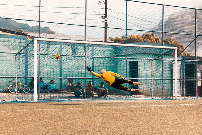 A soccer photography shot of a goalkeeper trying to save a goal