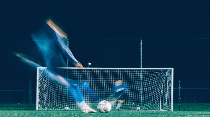 Artistic soccer photography shot of a blurry player on the field at night