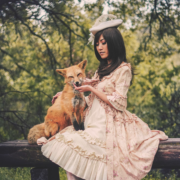 A vintage style portrait of a female model in old style costume holding a fox