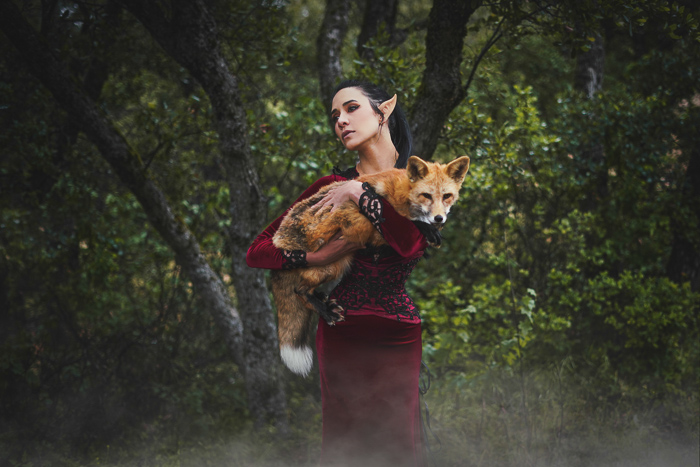 A fantasy themed portrait of a female model in elf costume holding a fox
