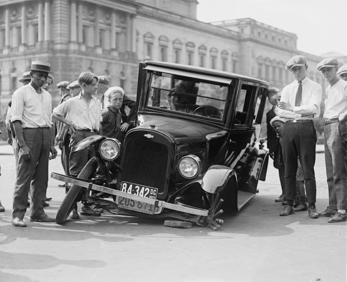 black and white vintage photography of a group of men and boys standing around a broken down vintage car