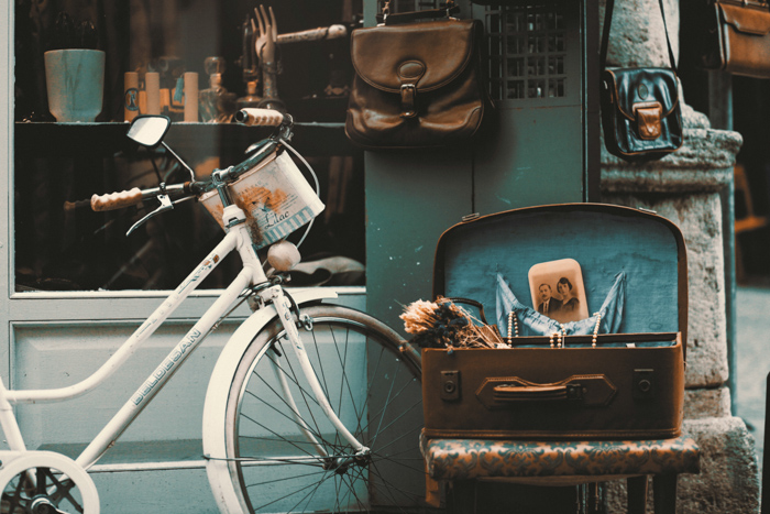 an outdoor still life of antiques such as a bicycle, leather bags and photos - vintage photography tips