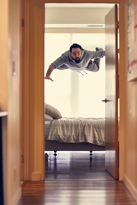 A funny photography portrait of a man levitating over his bed