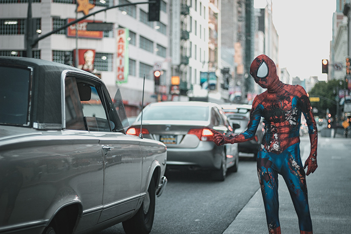 A funny photography portrait of spiderman hailing a cab