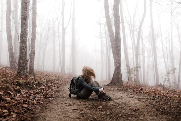 Atmospheric portrait of a girl sitting in a forest edited using Lightroom dehaze feature