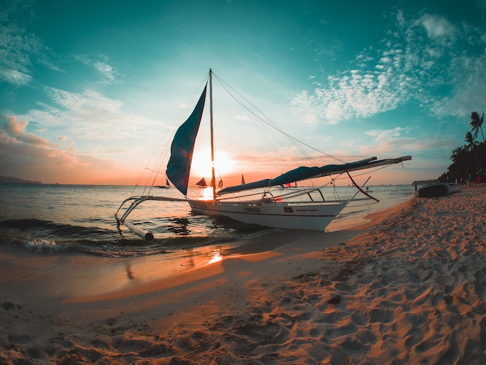 a beautiful sunset shot of a boat on a beach using the teal and orange color scheme