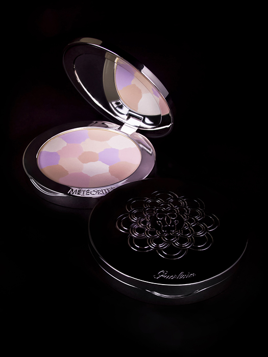 A makeup product shot of compact powder against black background