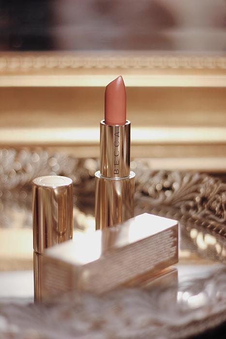 Una elegante foto de un producto de maquillaje de Becca Lipstick en un lujoso plato