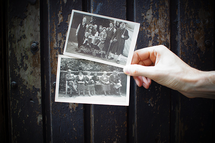 a hand holding two old photographs