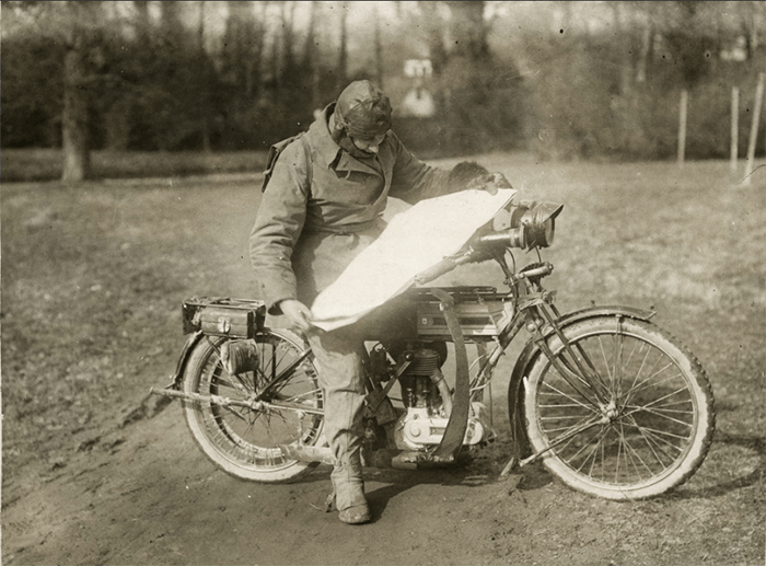 Old sepia toned photo of a man on a motor bike