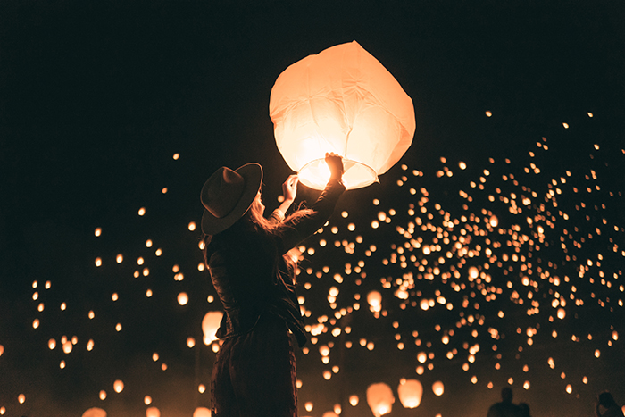 Dreamy night portrait of a girl lighting a sky lantern