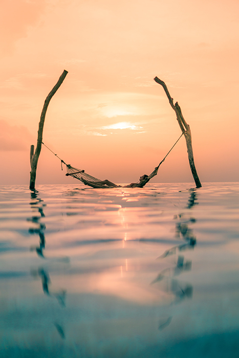 dreamy shot of a person resting on a hammock in the sea at sunset