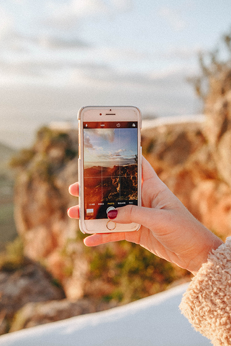A person taking a landscape photo on their smartphone, using the rule of thirds grid