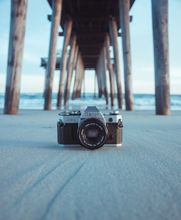 a canon film camera outdoors under a wooden pier