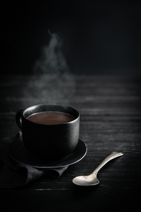 Stylish drink photo of a cup of steaming coffee against a dark background