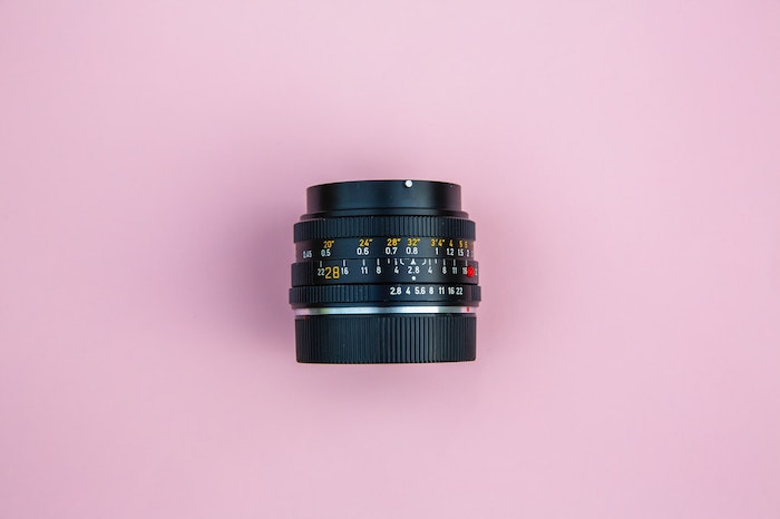 overhead shot of a camera lens on pink background - best lens for product photography