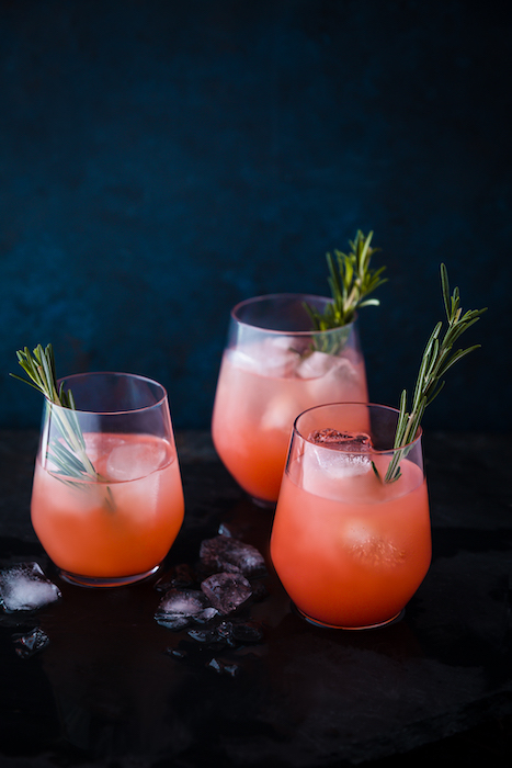 Stylish drink photo of three orange cocktails against a dark background