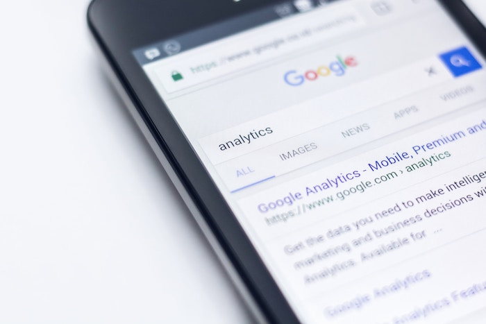 a close up of a smartphone screen with 'analytics' typed in google - seo for photography
