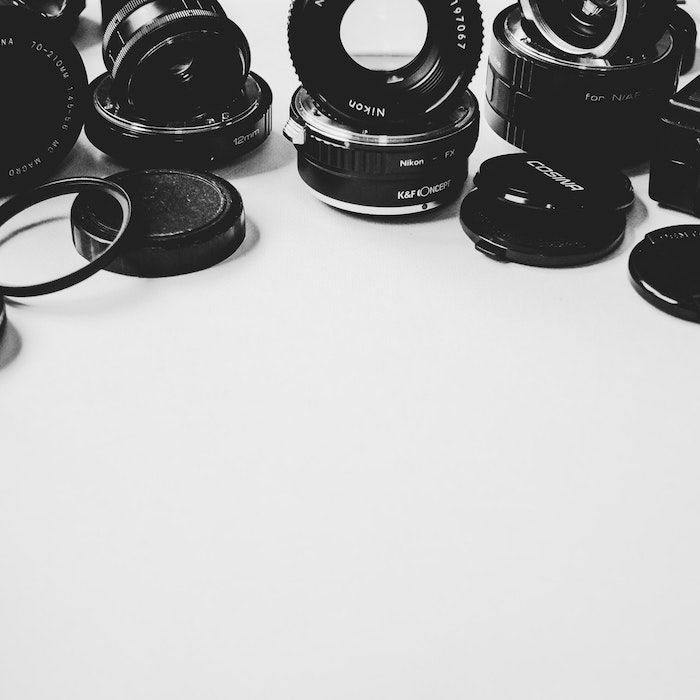 a still life of different lenses and lens caps - best lens for product photography