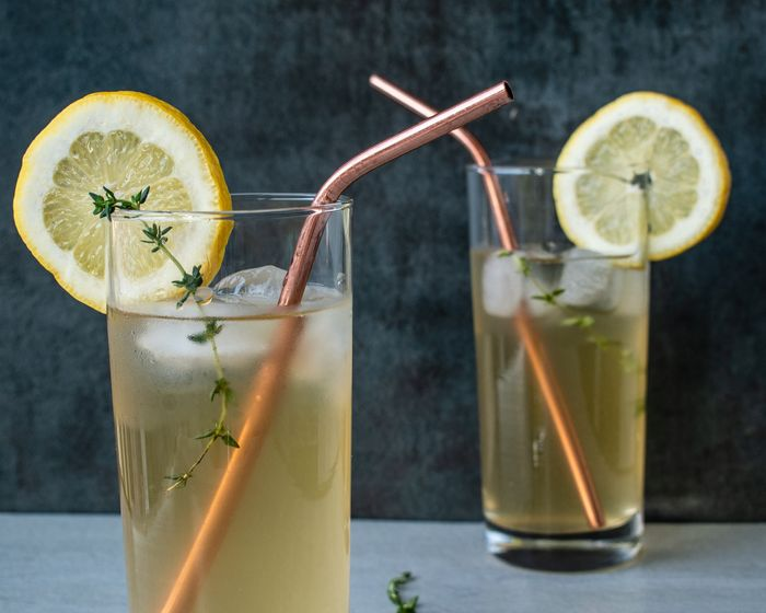 a photo of two glasses of lemonade with ice cubes and straws