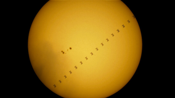 The ISS transiting in front of the Sun, passing next to a group of sunspots