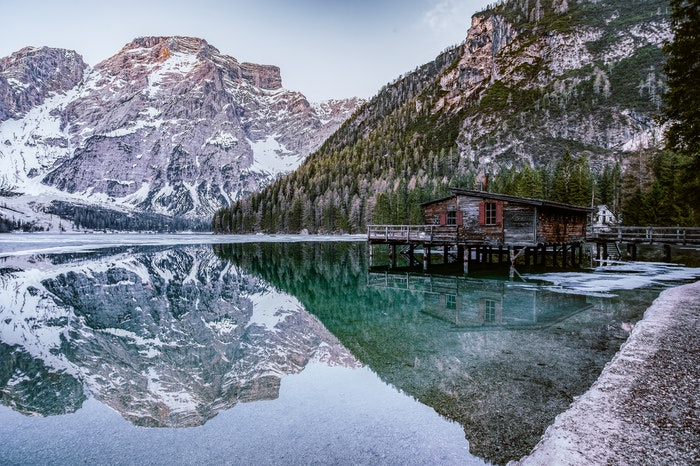 a long cabin over a lake surrounded by mountains, utilizing dynamic range in photography