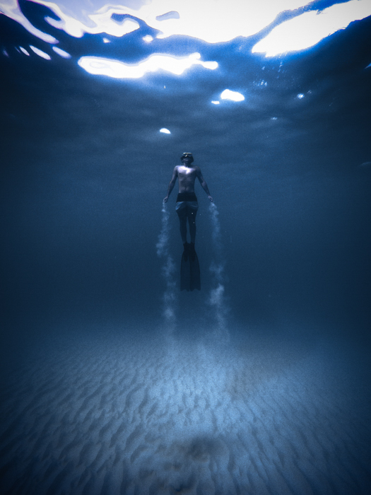 an underwater portrait of a diver with vignette effect