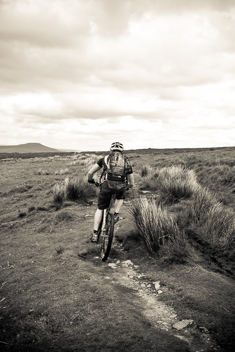 monochrome shot of a cyclist moving through a landscape - adventure photography skills