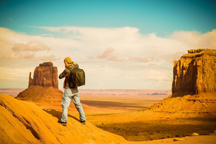 a hiker standing on a rocky desert landscape - adventure photography skills