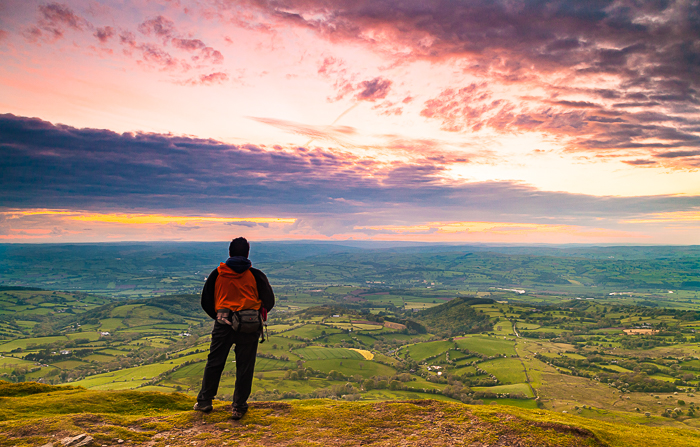 a hiker admiring the sunset from a luscious landscape - adventure photography skills