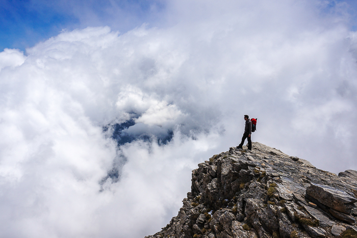 a hiker standing on the rocky peak of a mountainous landscape - adventure photography skills