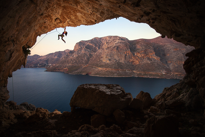 a rockclimber above a cave by water and a mountainous landscape - adventure photography skills