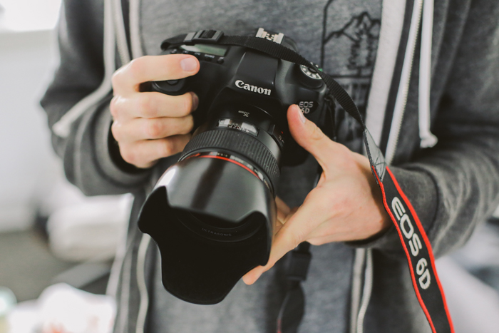 a photographer holding a canon dslr - find camera manuals online