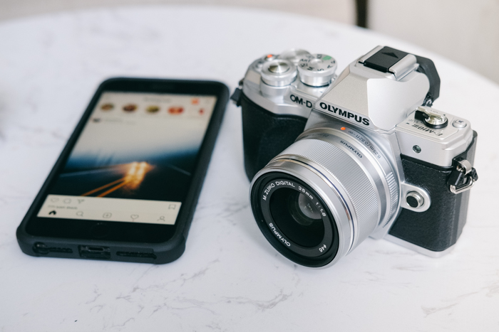 an olympus camera beside a smartphone - find camera manuals online