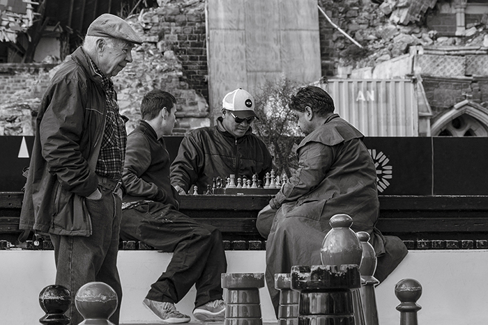 candid street photo of people playing chess outdoors